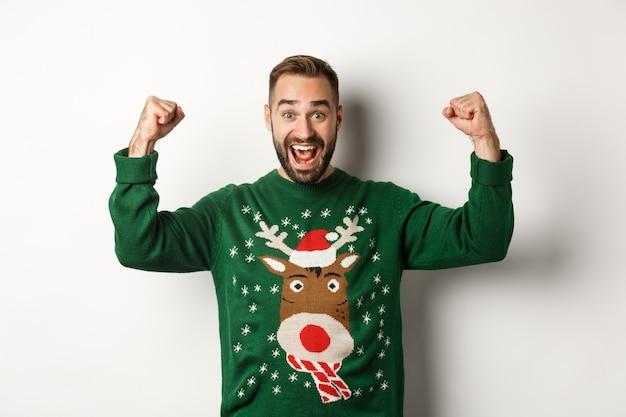新年、祝日、お祝い。クリスマスセーターを着て、手を上げて祝い、勝利し、白い背景の上に立って、安心して興奮した男