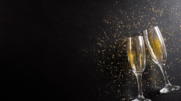 New year holidays background concept made from champagne glasses with golden glitter