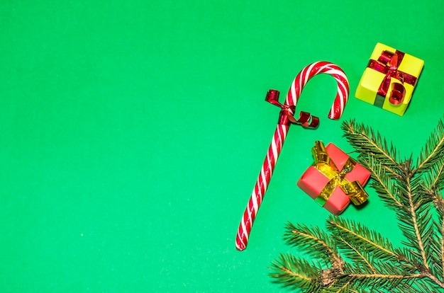 New year, holidays, celebration concept. gifts on green background. christmas tree gifts, candy cane. flat lay, copy space
