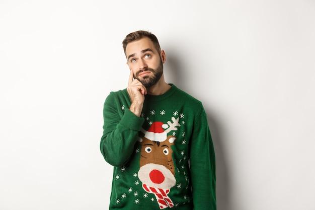 Capodanno, vacanze e celebrazione. giovane triste con la barba, che indossa un maglione verde, che mostra una lacrima sul viso e alza lo sguardo sconvolto, in piedi su sfondo bianco