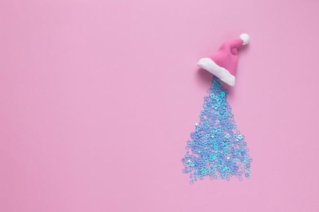 새 해 휴일 개념 창조적 인 반짝이 크리스마스 트리 산타 클로스 모자를 쓰고 컬러 배경, 복사 공간 평면도