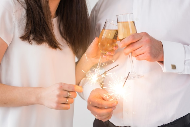 New year, holidays, date and valentines day concept - loving couple holding sparklers light
