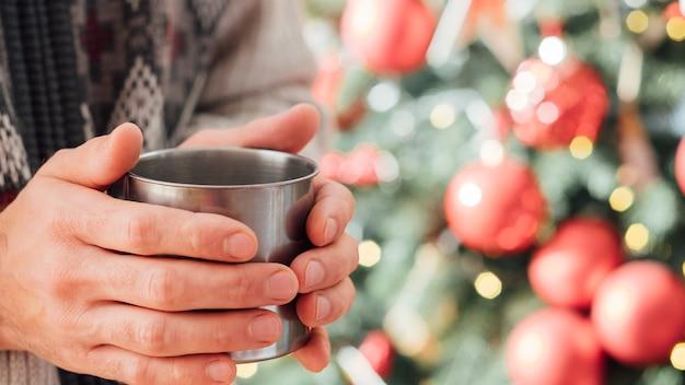 新年の家のお祝い。ぼやけて装飾されたモミの木の上に鋼のマグカップで熱い飲み物を保持している男の手のクローズアップ。