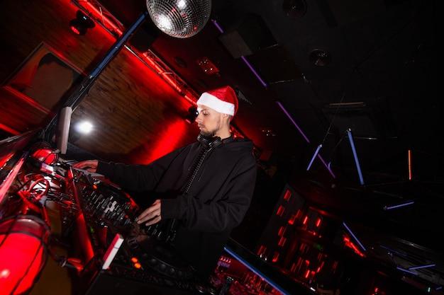 나이트 클럽에서 새해. 크리스마스 파티에서 턴테이블에 음악을 믹싱하는 빨간 산타클로스 모자를 쓴 젊은 자신감 있는 dj. 빛나는 디스코 볼. 검정과 빨강 클럽 배경입니다.