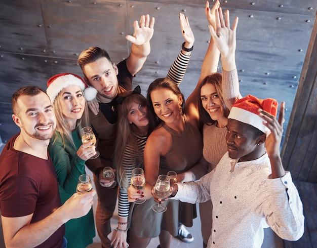 新年が来ています!感情的なライフスタイルの人々の概念をポーズ、パーティーのサンタ帽子で陽気な若い民族の人々のグループ