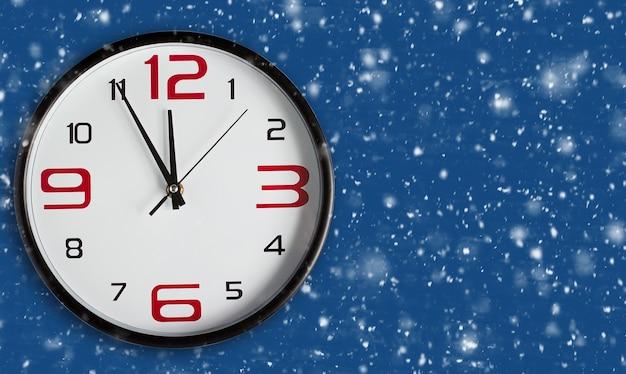 Скоро новый год. большие настенные часы на классическом синем фоне. поздравительная открытка с рождеством и новым годом на синем фоне снега с копией пространства. новый цветовой тренд 2020 года