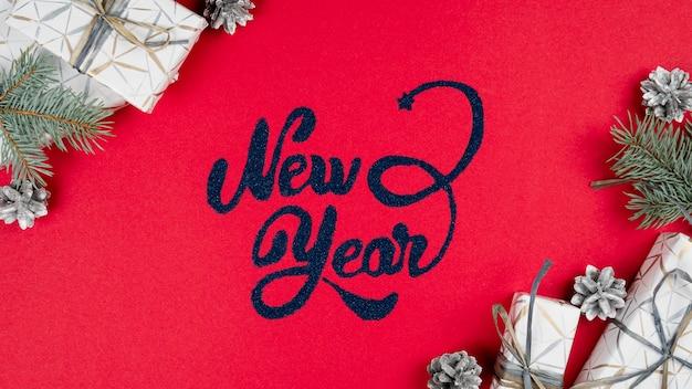 赤、モミの木の枝、銀の円錐形、周りのギフトボックスに新年のレタリング