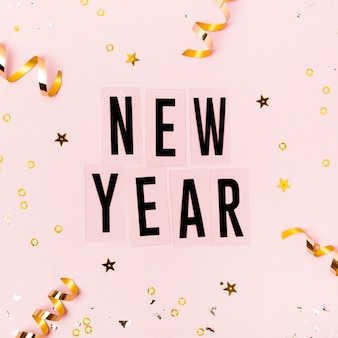 New year lettering on pink background with golden ribbons