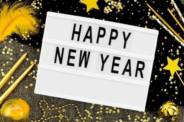 New year lettering on a white card with golden accessories