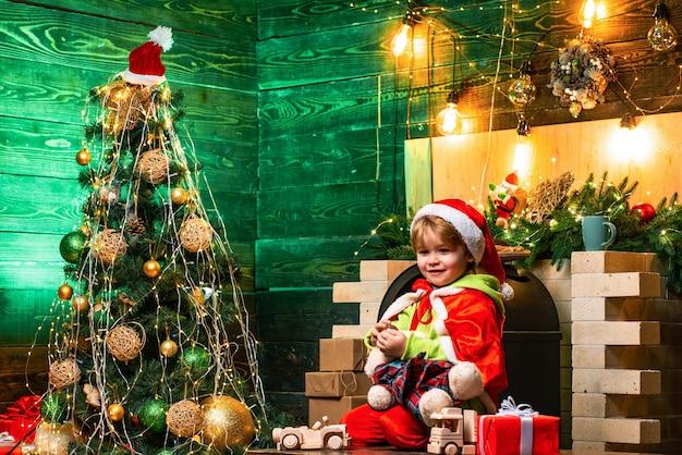 新年。サンタの帽子と衣装を着て楽しんでいる男の子。休日割引。飾る小さな男の子
