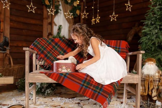 新年 。メリークリスマス、ハッピーホリデー。白いウサギのベンチとオープンボックスに座っている白いドレスの少女。夜のクリスマスツリーのインテリアの魔法の光