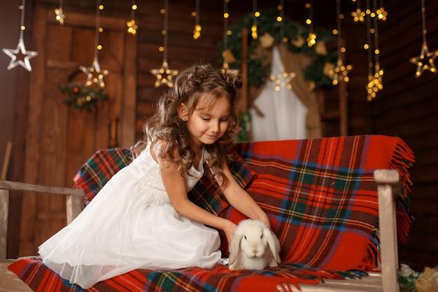 新年 。メリークリスマス、ハッピーホリデー。白いウサギとベンチに座っている白いドレスの少女。夜のクリスマスツリーのインテリアの魔法の光