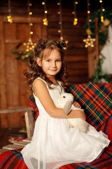 新年 。メリークリスマス、ハッピーホリデー。夜クリスマスツリーインテリアの小さな女の子魔法の光のクローズアップの肖像画