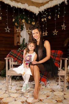 New year . merry christmas, happy holidays. a little girl in white dress sitting on the bench with mum. magic light in night xmas tree interior.