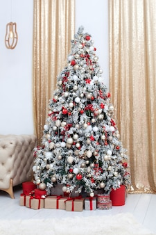 New year. merry christmas and happy holidays. stylish living room interior with decorated christmas tree and comfortable sofa.