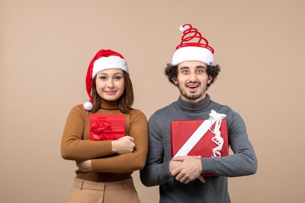 Новогоднее настроение и концепция вечеринки - молодая взволнованная милая пара в шляпах санта-клауса на сером