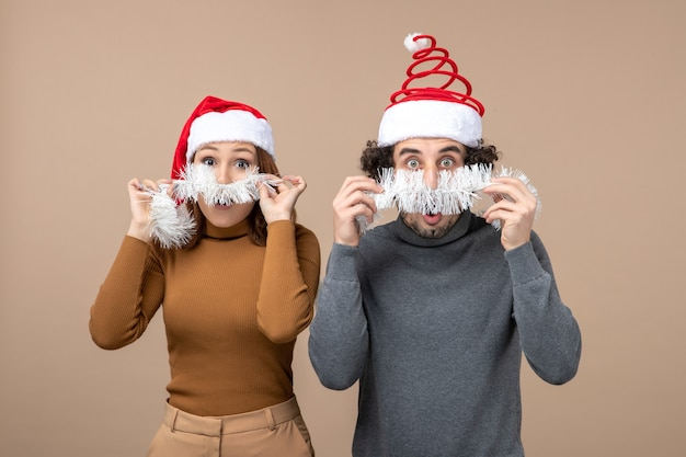 Concetto festivo di umore del nuovo anno con le coppie adorabili soddisfatte fresche eccitate che portano i cappelli rossi del babbo natale sull'immagine di riserva grigia