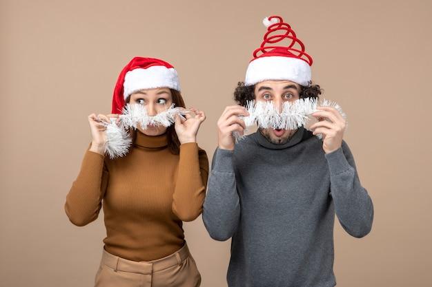 Concetto festivo di umore del nuovo anno con le coppie adorabili soddisfatte fresche eccitate che portano i cappelli rossi del babbo natale su gray
