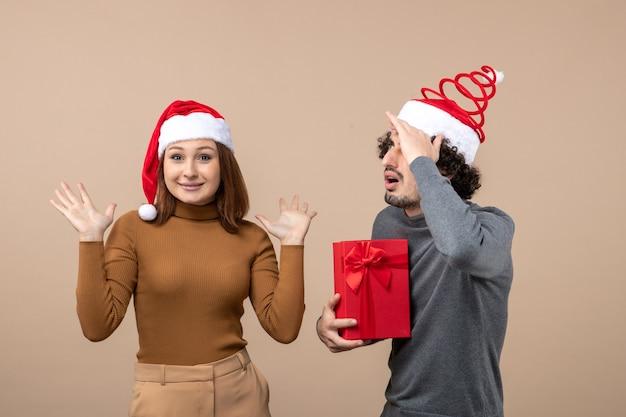 灰色の赤いサンタクロースの帽子をかぶって面白い幸せな集中素敵なカップルと新年気分お祝いのコンセプト