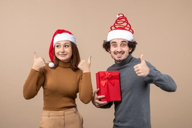 Праздничная концепция новогоднего настроения с забавной счастливой прекрасной парой в красных шляпах санта-клауса, делающей идеальный жест на сером
