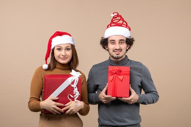 灰色の赤いサンタクロースの帽子をかぶって面白い幸せな満足の素敵なカップルと新年気分お祝いのコンセプト
