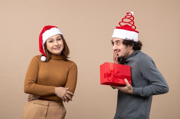 Il concetto festivo dell'umore del nuovo anno con le coppie adorabili divertenti che portano la ragazza rossa dei cappelli di babbo natale ha dato il suo regalo sul grigio