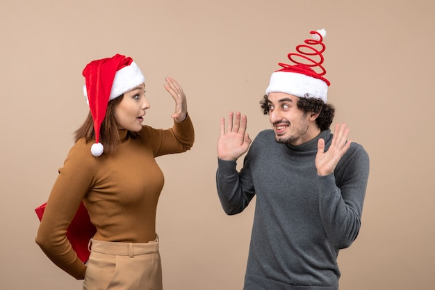 Concetto festivo di umore del nuovo anno con coppia adorabile divertente che porta il regalo nascosto della ragazza dei cappelli di babbo natale rosso dietro su gray