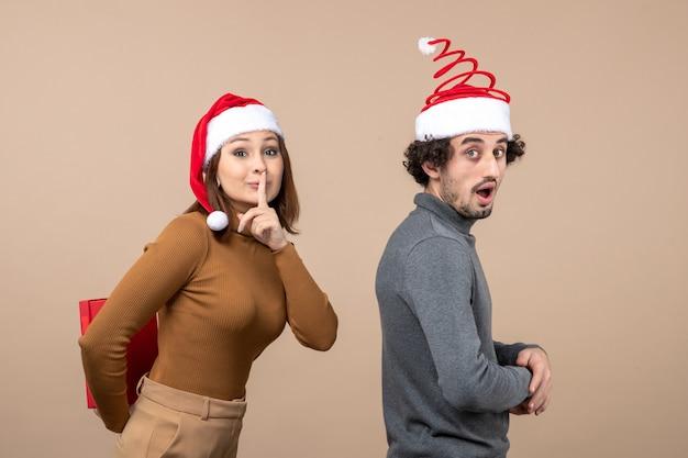 Concetto festivo di umore del nuovo anno con coppia adorabile divertente che porta la ragazza rossa dei cappelli di babbo natale che fa sorpresa