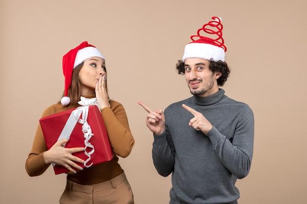 Concetto festivo di umore del nuovo anno con le coppie adorabili divertenti che portano i cappelli rossi del babbo natale su gray