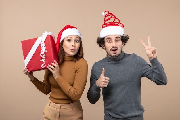 灰色の赤いサンタクロースの帽子をかぶっている面白い素敵なカップルと新年気分お祝いのコンセプト