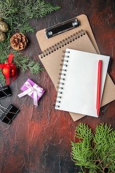 暗い背景にペンでノートの横にある新年気分モミの枝の装飾アクセサリーとギフト