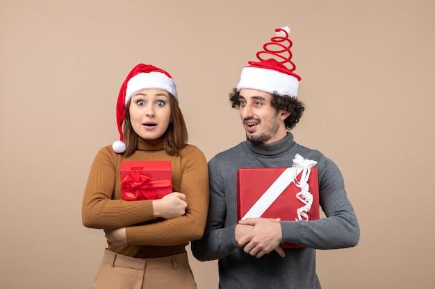 Concetto di umore e festa del nuovo anno - giovani regali adorabili emozionanti della tenuta delle coppie che portano i cappelli di babbo natale su gray