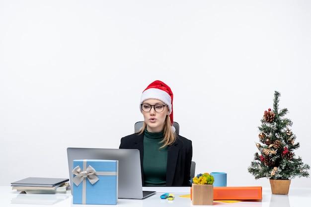 Umore del nuovo anno con una donna attraente con un cappello di babbo natale seduto a un tavolo con un albero di natale e un regalo su di esso su sfondo bianco