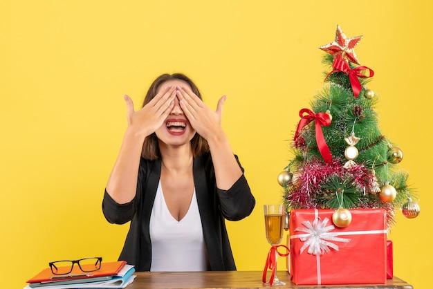 행복하게 그녀의 눈을 감고 사무실의 테이블에 앉아 아름다운 비즈니스 아가씨와 함께 새해 분위기