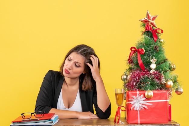 何かについて混乱し、オフィスのテーブルに座っている美しいビジネスレディと新年の気分