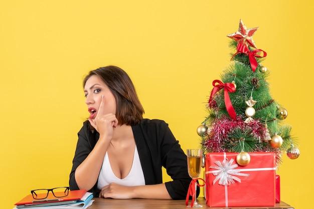 Umore del nuovo anno con una bella donna d'affari in pensieri profondi e seduta a un tavolo in ufficio