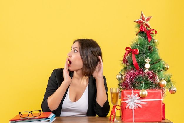 意外と何かを見て、オフィスのテーブルに座っている美しいビジネスレディと新年の気分