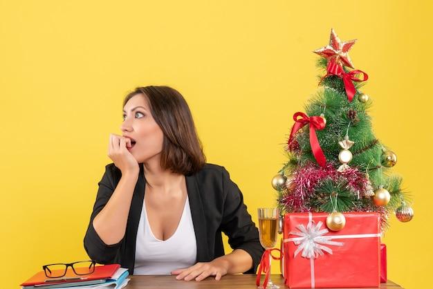 Umore del nuovo anno con una bella donna d'affari che guarda qualcosa di sorprendente e si siede a un tavolo in ufficio