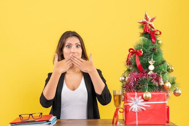 沈黙のジェスチャーをし、オフィスのテーブルに座っている美しいビジネスレディと新年の気分