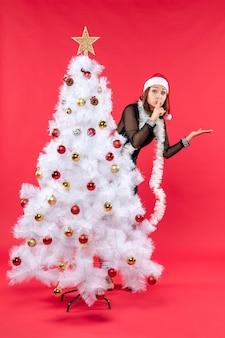 Новогоднее настроение с красивой девушкой в черном платье с шапкой санта клауса, прячущейся за елкой
