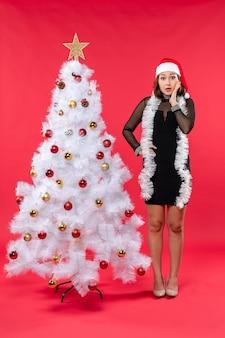 산타 클로스 모자를 쓴 검은 드레스에 그녀의 깜짝 놀라움을 숨길 수없는 아름다운 소녀와 함께하는 새해 분위기