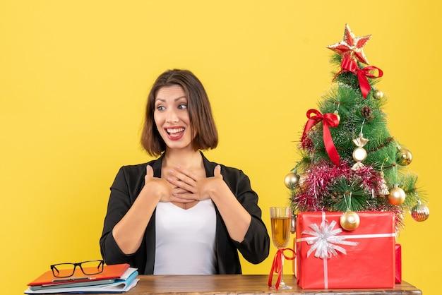 意外と自分を指差してオフィスのテーブルに座っている美しい幸せなビジネスレディと新年の気分