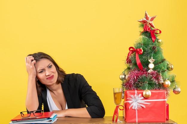 何かについて混乱し、オフィスのテーブルに座っている美しい真面目なビジネスレディと新年の気分