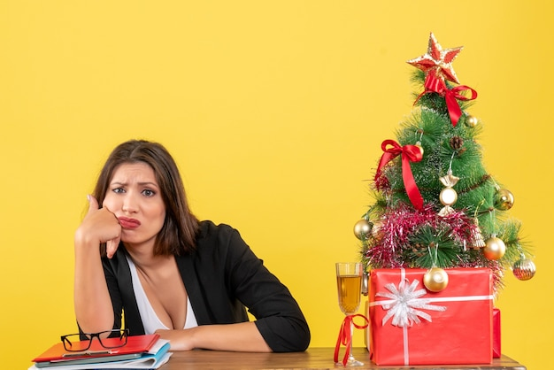 Umore del nuovo anno con una bella signora d'affari insoddisfatta confusa su qualcosa e seduta a un tavolo in ufficio