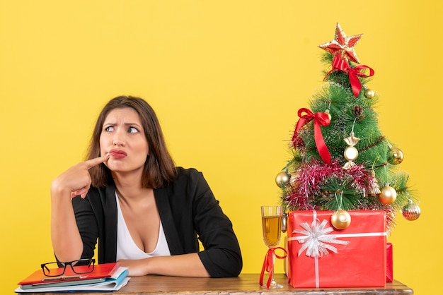 何かについて混乱し、オフィスのテーブルに座っている美しい不満の驚きのビジネスレディと新年の気分