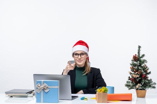 Umore di capodanno con donna bionda con un cappello di babbo natale seduto a un tavolo con un albero di natale e un regalo su di esso su sfondo bianco
