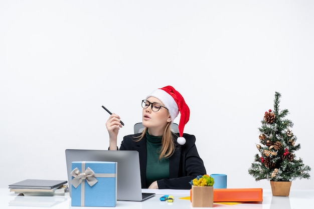 New year mood with concentrated blonde woman with a santa claus hat sitting at a table with a christmas tree and a gift on it on white background