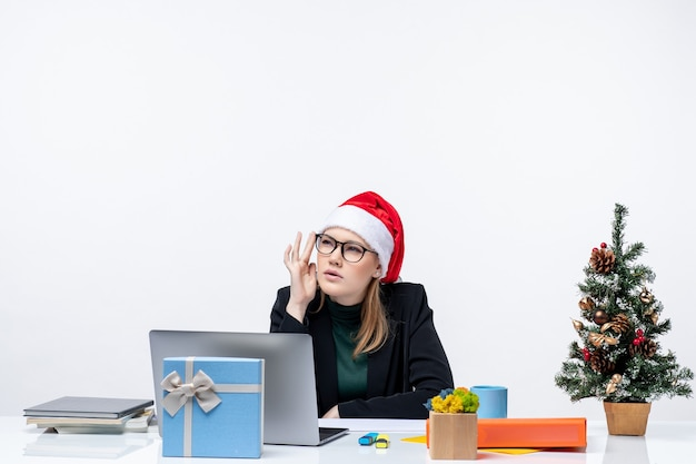 New year mood with confused attractive woman with a santa claus hat sitting at a table with a christmas tree and a gift on it in the office