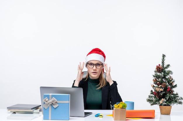 Umore del nuovo anno con la donna confusa con un cappello di babbo natale seduto a un tavolo con un albero di natale e un regalo su di esso su sfondo bianco