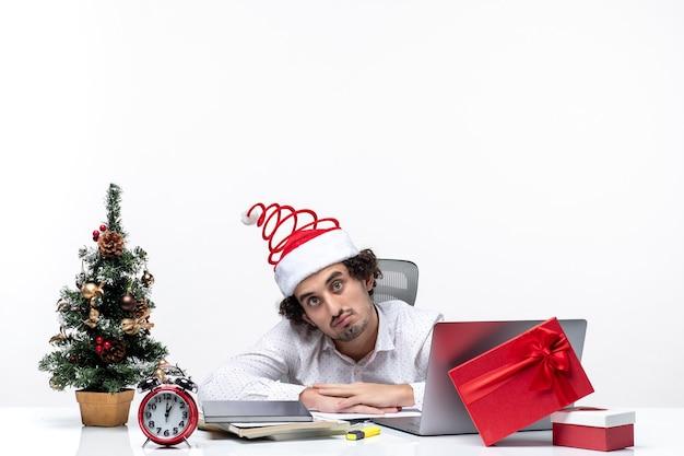 Umore del nuovo anno con il giovane uomo d'affari confuso con il cappello di babbo natale divertente che si sente sorpreso in ufficio su priorità bassa bianca